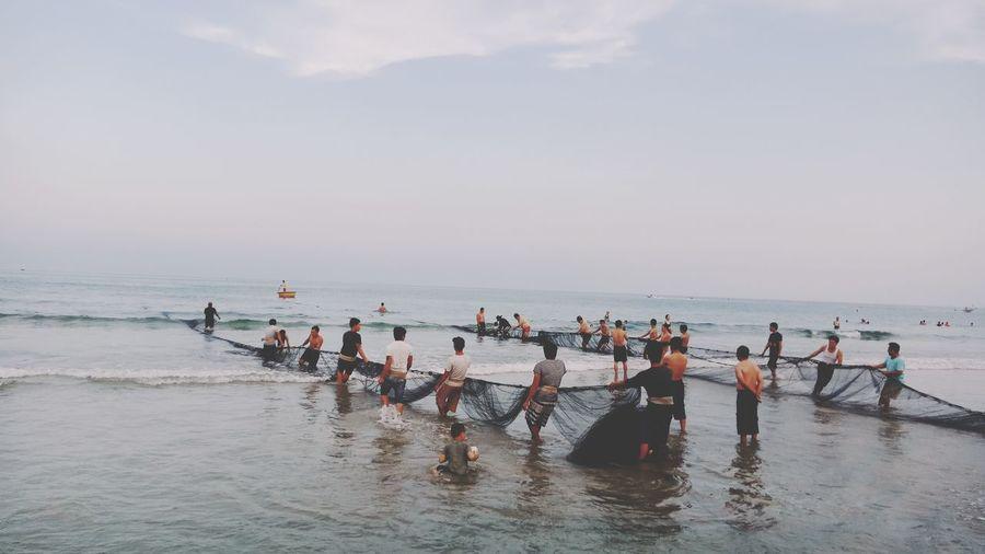 Fishermen pulling fishing net on shore at beach against sky