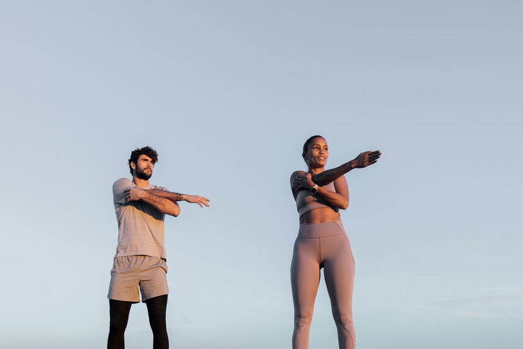 Low angle view of friends standing against clear sky