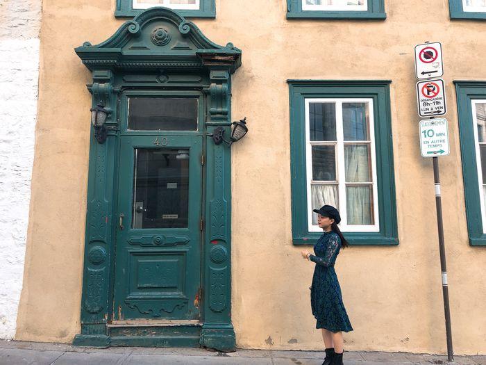 Side view of woman standing against door of building