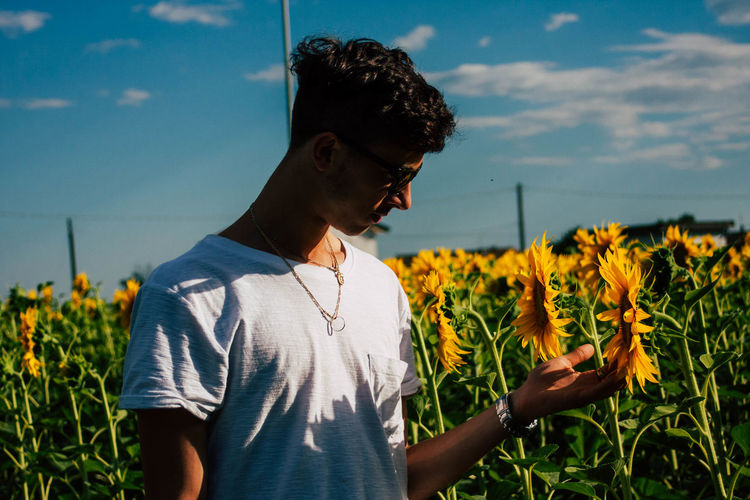Young man touching sunflower on field against sky during sunny day