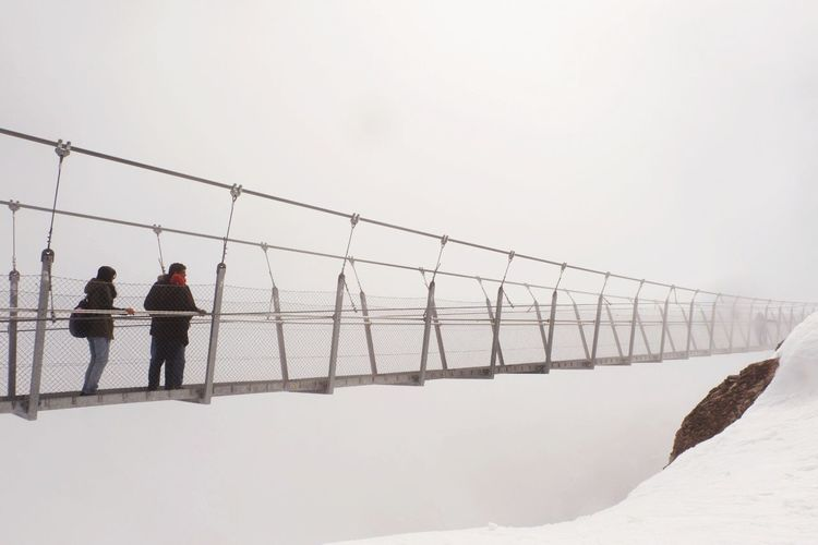 Family Standing On Footbridge By Snowcapped Mountain Against Clear Sky
