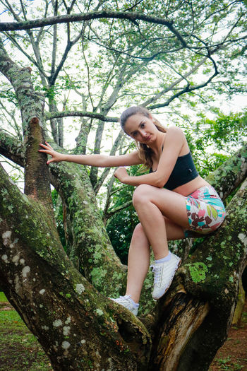 Low angle view of young woman on tree
