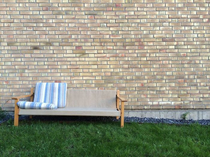 Sofa On Lawn Of House Against Brick Wall