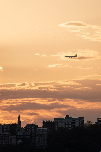 Airplane flying over buildings in city against sky during sunset