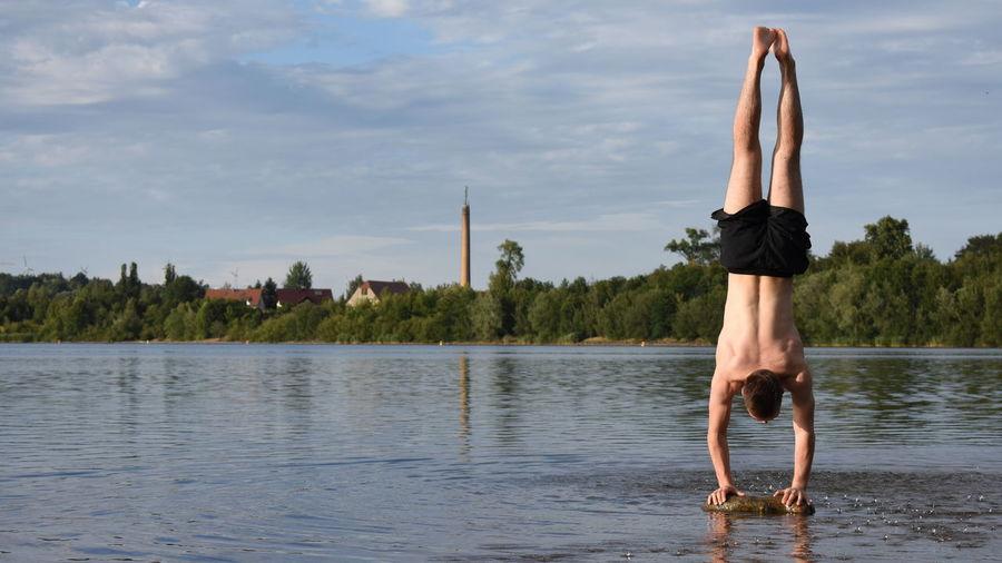 Full length of shirtless man on lake against sky