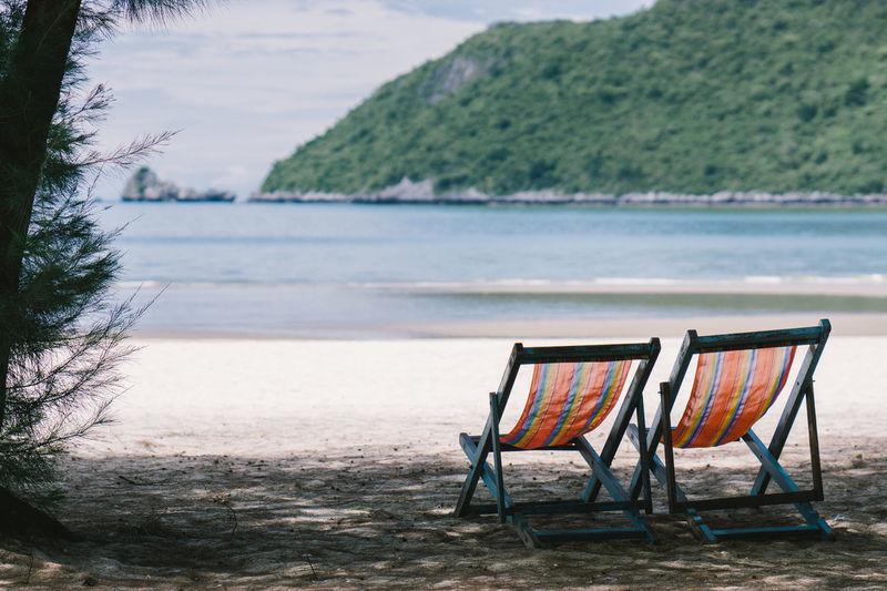 Chairs on beach against mountain
