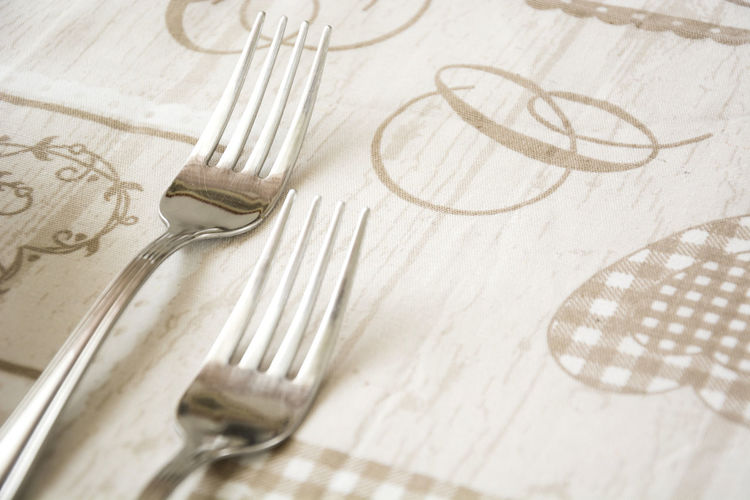 Close-up of forks on tablecloth