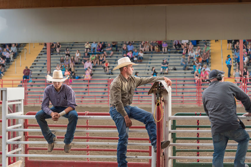 Williams Lake, British Columbia/Canada - June 30, 2016: cowboys and volunteers watch the competitors from behind the chutes at the 90th Williams Lake Stampede, one of the largest in North America. 90th Williams Lake Stampede Behind The Scenes British Columbia, Canada Canadian Professional Rodeo Association Cowboys Rodeo Spectators Travel Audience Boy Candid Chutes Competition Country Western Crowd Documentary Editorial  Men Professional Rodeo Stampede Stampede Grounds Stands Tourism Watching Western Dress