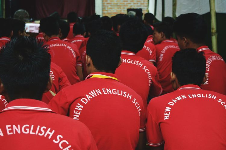 Rear View Of Boys In Red Uniform At School