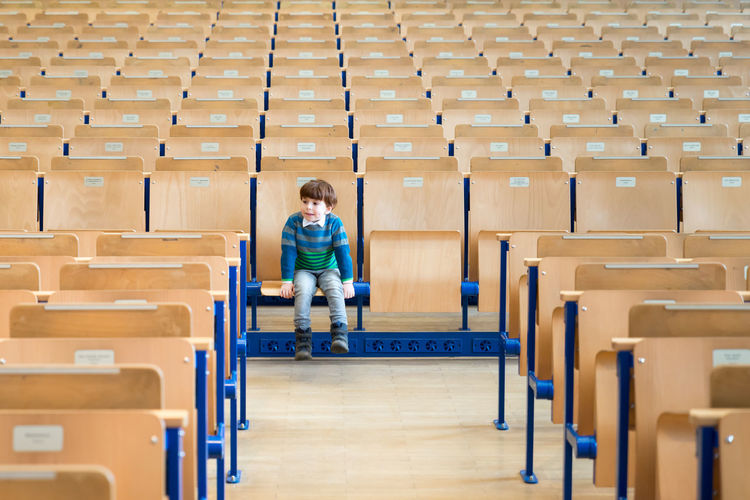 Kid sits alone in an empty university lecture hall, auditorium. Academics Alone Higher Education Lesson Student Academy Casual Clothing Chair Class Education Front View Full Length Indoors  Learning Lecture Lecture Hall One Person Pattern Real People Rows Of Things Seat Sitting University Wood - Material