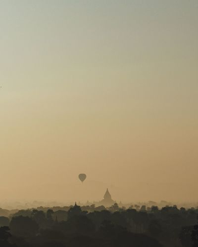Mid distance view of hot air balloon and temple during sunset