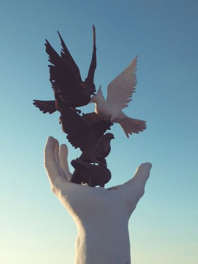 Hand of peace monument against sky