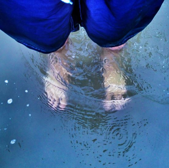 Man standing ankle-deep in water