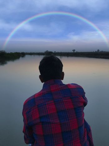 Rainbow Real People Water Rear View Leisure Activity Lifestyles Beauty In Nature Nature Sky Reflection One Person Scenics Double Rainbow Standing Outdoors Men Day Multi Colored