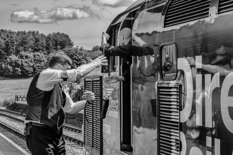 Class 37 diesel engine train passes through Weybourne Station, Norfolk, UK. The tokens are exchanged while the train is in motion, captured on ISO 200, 50mm, f/6.3 1/400 sec. The North Norfolk Railway is staffed by volunteers. Token Exchange Train Platform Uniform Vintage Style Black And White Black And White Collection  Black And White Train Class 37 Diesel Engine Diesel Locomotive Locomotive Locomotive Engine Men Mode Of Transportation Old Train Rail Transportation Railway Real People Token Train Station Transportation Vintage Photo Volunteer Work Volunteers