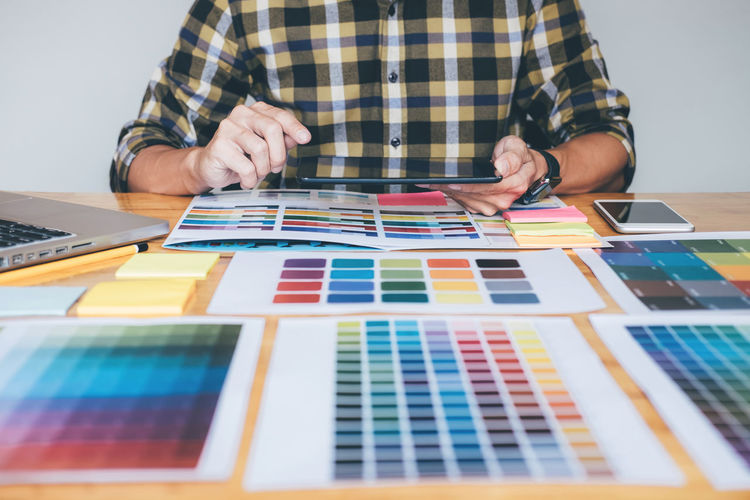 Architecture Choosing Adult Art And Craft Casual Clothing Checked Pattern Color Chart Colorful Creativity Designer  Front View Graphic Design Holding Human Hand Indoors  Leisure Activity Lifestyles Men Multi Colored One Person Pantone Screen Sitting Swatch Table