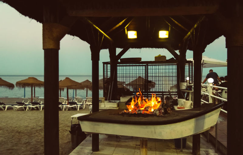 Sea Nature Architecture Water Burning Fire - Natural Phenomenon Fire Flame Built Structure Group Of People Beach Land Food And Drink Tourism Outdoors Wood Espeto Fish Food Cooking Typical Costa Del Sol Malaga Sunset Chiringuito