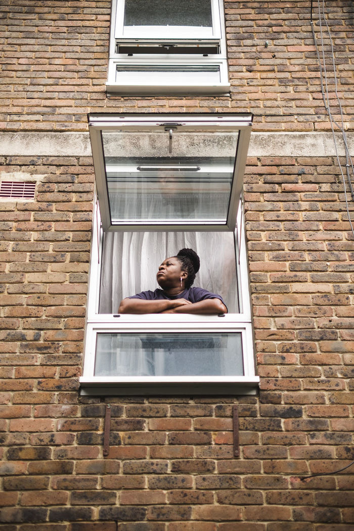 PORTRAIT OF YOUNG WOMAN LOOKING AT WINDOW