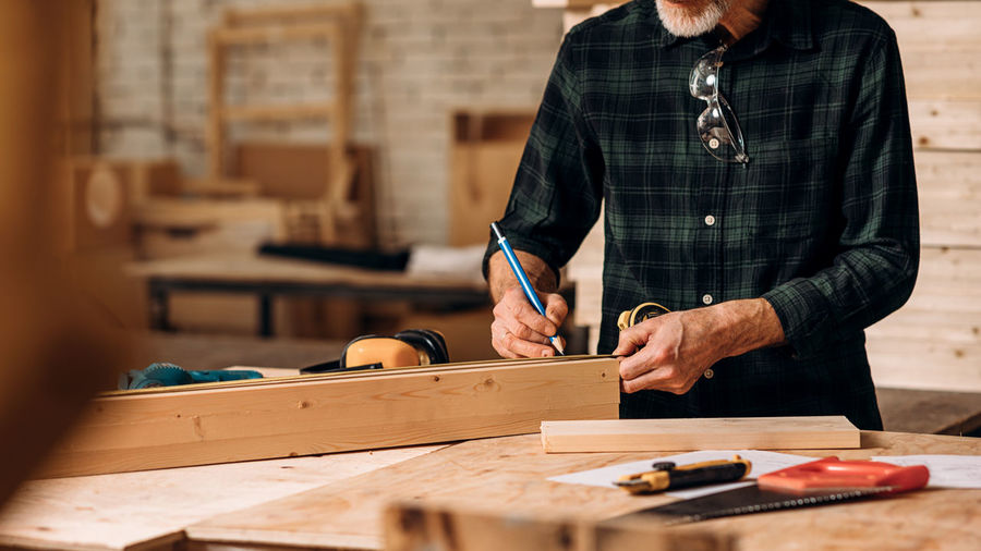 Midsection of carpenter working in workshop