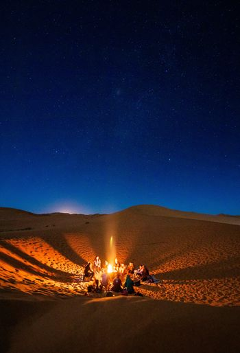 Group Of People By Campfire On Landscape Against Sky At Night