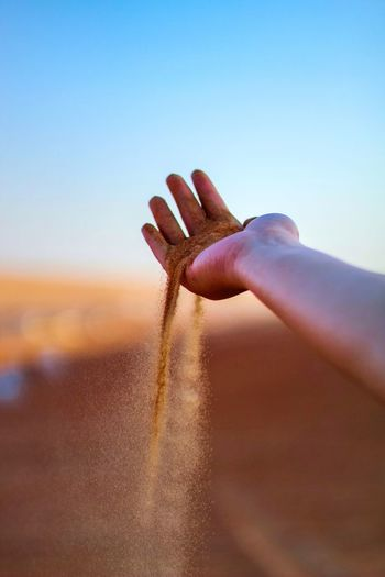 Close-up of hands against clear sky