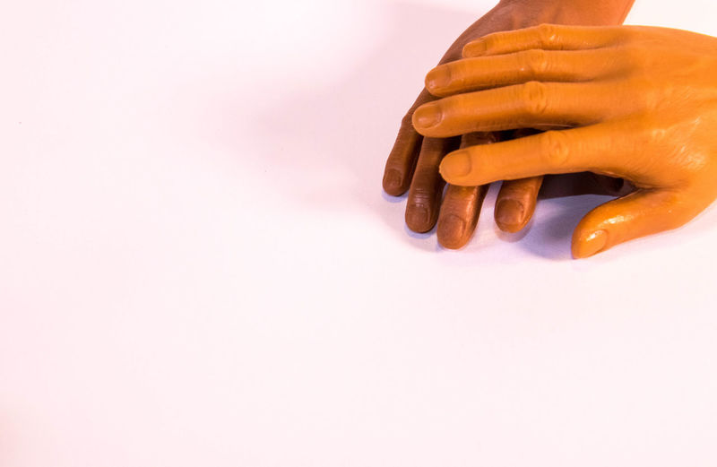 Close-up of hand on table against white background