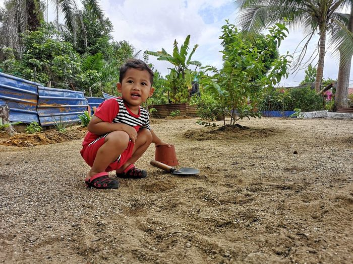 Cute boy looking away while crouching on sand