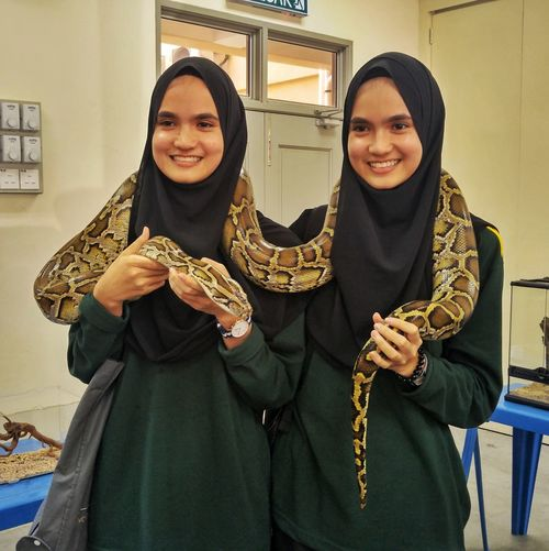 Twin with snake around the neck Reptile Brave Twin Snake Scary Cute Young Women Friendship Portrait Togetherness Smiling Females Women Standing Looking At Camera Saxophone