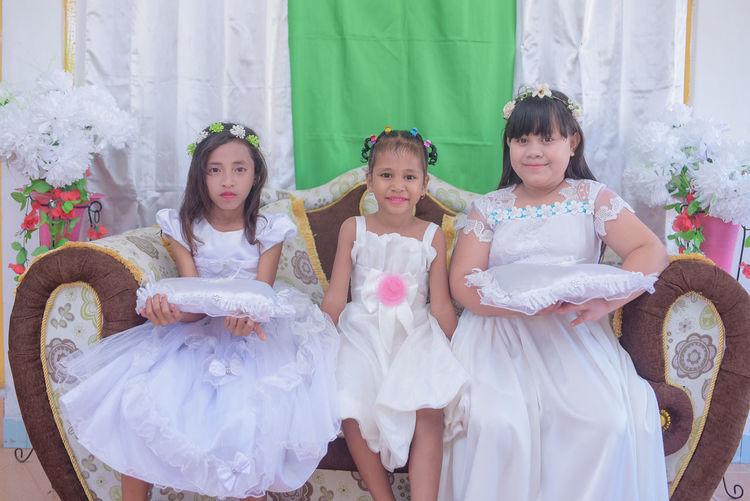 Portrait of girls wearing white dresses sitting on sofa at wedding ceremony