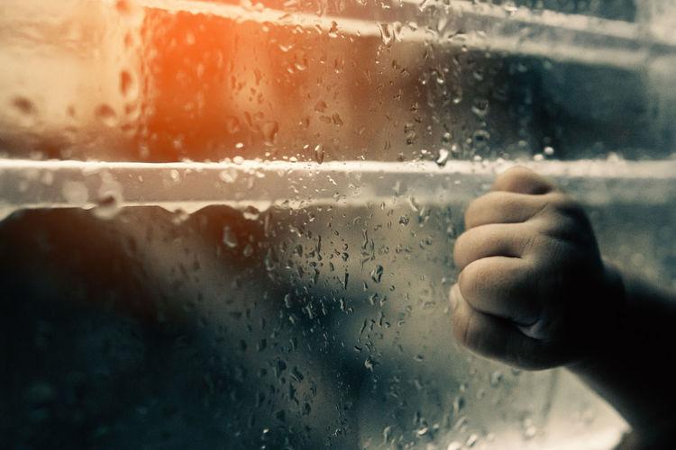 Close-up of hand holding glass window in rainy season