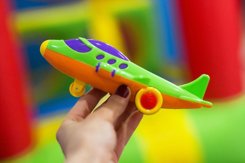 Young women holding a toy airplane Imaginary Imagination Exploring Plane Adventure Travel Destinations Dreaming Playing Travel Exploration Tourism Planning A Trip Bright Colors Dream Tour Pilot Human Hand Hand Multi Colored One Person Close-up Holding Creativity Lifestyles Personal Perspective Toy