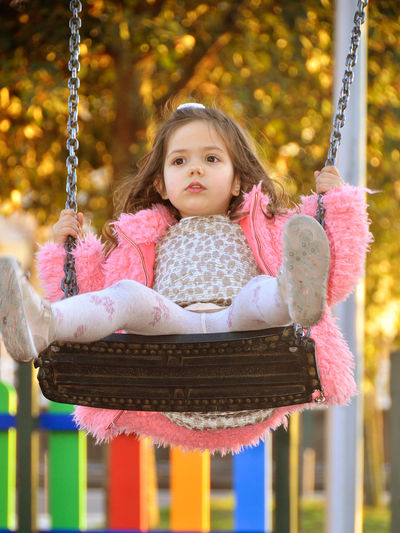 3-4 years girl playing on swing Carousel Child Childhood Children Only Close-up Day Front View Girls Hanging Leisure Activity One Girl Only One Person Outdoor Play Equipment Outdoors People Playground Rope Swing Sitting Swing
