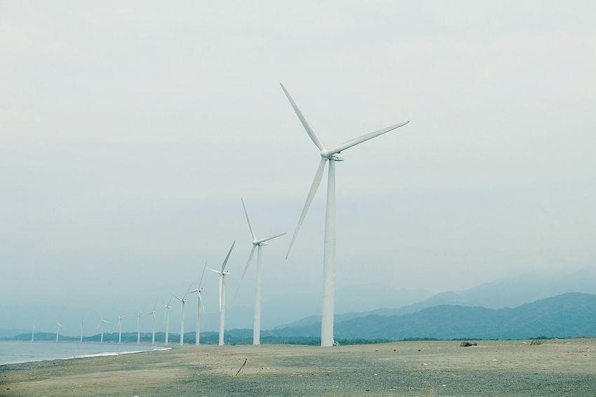Fuel And Power Generation Renewable Energy Environmental Conservation Windmill Wind Turbine Wind Power Alternative Energy Rural Scene Environment Clear Sky Power In Nature Sky Solitude Cloud Water Sea Shore Nature Tranquility In A Row