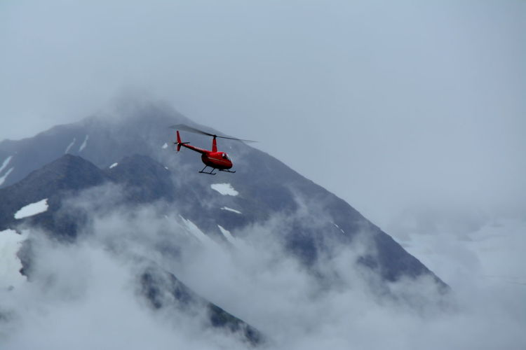 Adventure Alaska Cloud - Sky Flying Foggy Freedom Helicopter In Flight Journey Low Angle View Mid-air Mode Of Transport Mountain Mountains And Sky Nature Outdoors Red Remote Rugged Scenics Showcase July Sky This Week On Eye Em This Week On Eyeem Transportation