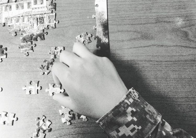 Cropped Hand Of Person Playing Puzzle At Table