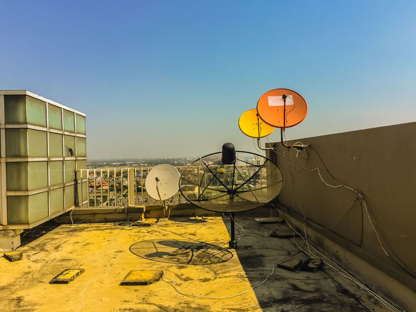 Old satellite dishes on concrete deck top roof floor of the old condominium building Rooftop Satellite Antennas Satellite TV Antenna Satellite Tv Architecture Built Structure Clear Sky Concrete Deck Condominium Day Nature No People Outdoors Satellite Dish Satellite Dishes Satellitedish Sky Telecommunication Telecommunications Equipment Television Tower Top Roof Yellow