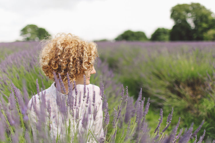 YOUNG WOMAN STANDING IN FIELD OF LAVENDER
