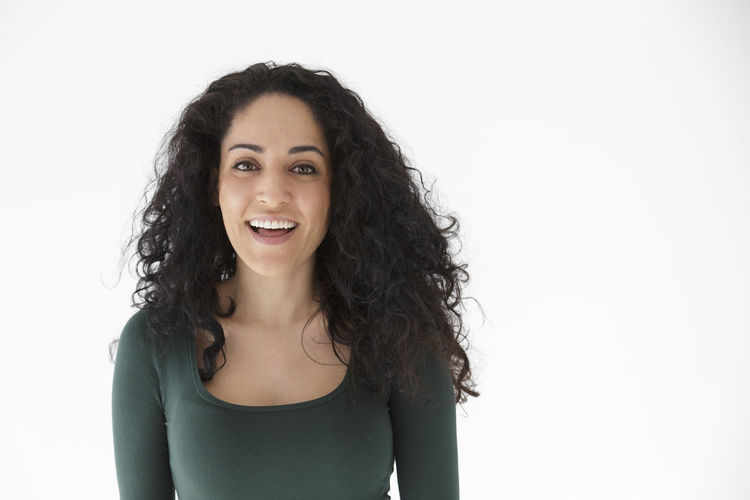 Adult Beautiful People Beautiful Woman Beauty Cheerful Confidence  Copy Space Curly Hair Front View Happiness Headshot Long Hair Looking At Camera One Person One Woman Only One Young Woman Only Only Women People Portrait Smiling Studio Shot Toothy Smile White Background Young Adult Young Women