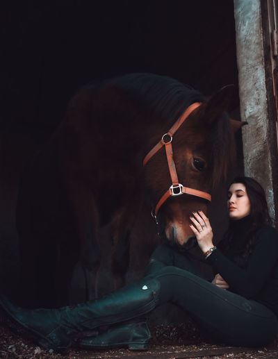 Woman sitting with horse at stable