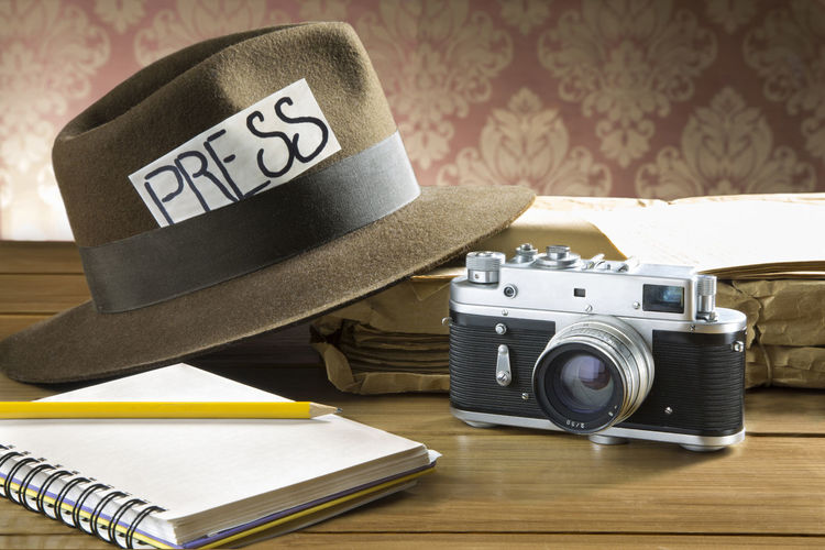 Press text on hat with diary and vintage camera on table