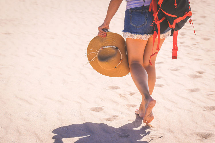 Close up view of a trendy girl walking barefoot on white sand. Jeans shorts and straw hat in her hand. Tourist woman walk on a exotic beach. - Back view - Travel adventure tourism and freedom concept. Alone Attractive Away Backpacker Beautiful Beauty Boho Carefree Caucasian Coast Cute Fashion Female Fitness Foot Fun Hair Happy Health Healty Holiday Legs Leisure Lifestyle Light Model Natural Nature Ocean One Outdoor Outdoors People person Pretty Relax Relaxation Sea Shore Sport Step Summer Sun Sunny Sunset Tropical Vacation Water Young