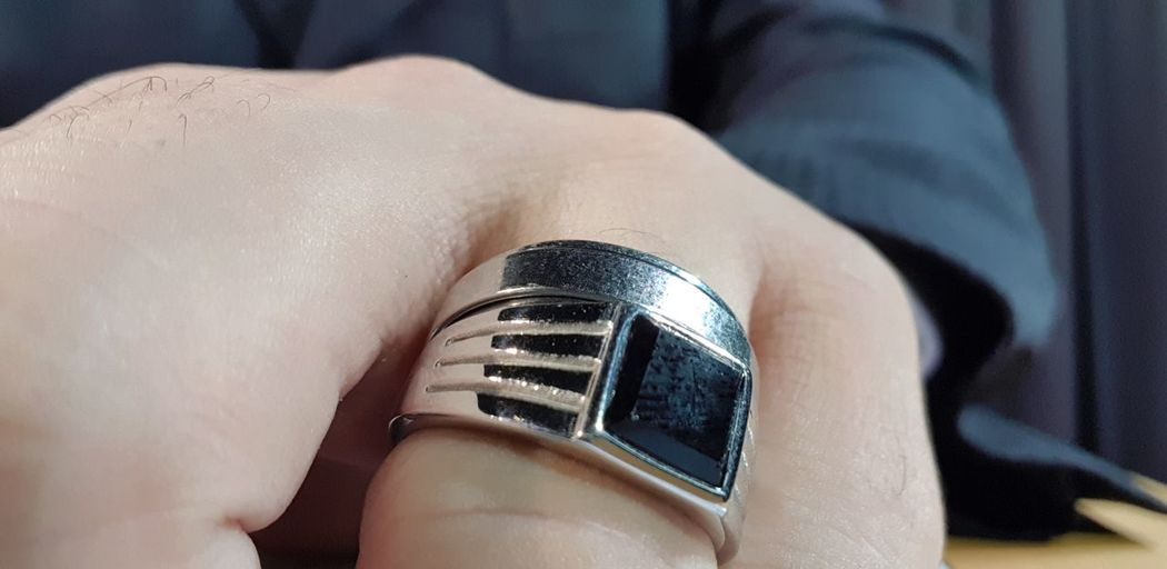 Cropped hand wearing ring at home