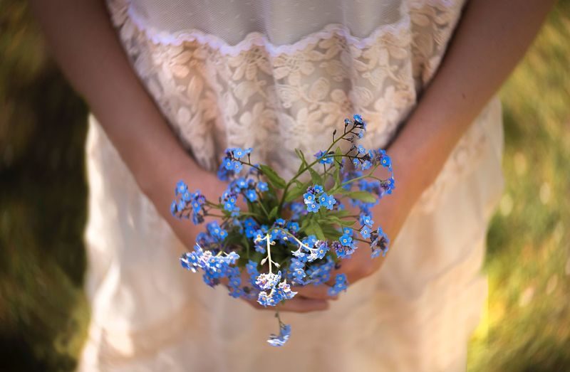 Midsection of woman holding flowering plant