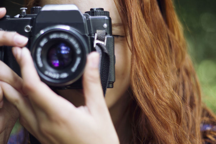 Cropped image of woman holding camera