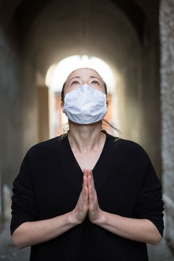 Portrait of woman wearing mask standing at home