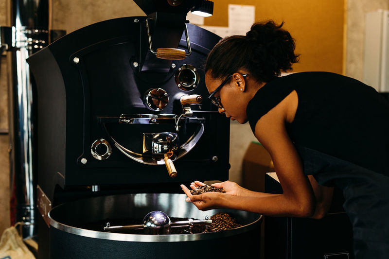 African American Beans Coffee Coffee Shop Females Machine Small Business Woman Working Young Barista Close Up Holding Indoors  Inspecting Lifestyles Occupation One Person Owner Process Real People Roasting Smelling