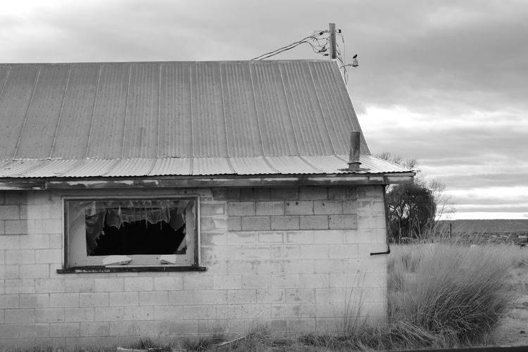 A broken down abandoned concrete block building photo rendered in black and white. Alturas Americana California Modoc County USA Architecture Bird Black And White Building Exterior Built Structure Corrugated Iron Day No People Outdoors Sky Tall Grass Trees And Sky Utility Pole