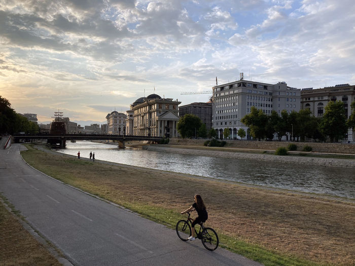 Bicycle by river against buildings in city
