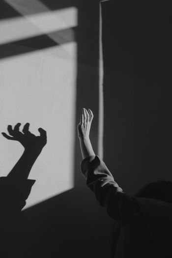 Woman with raised hand standing by shadow on wall