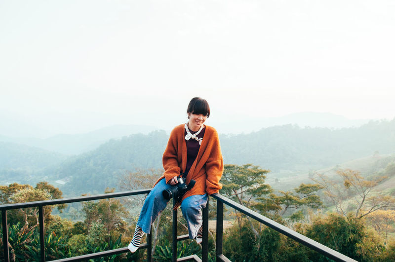 Young asian woman wearing casual clothes holding camera sit on fence at mountain top